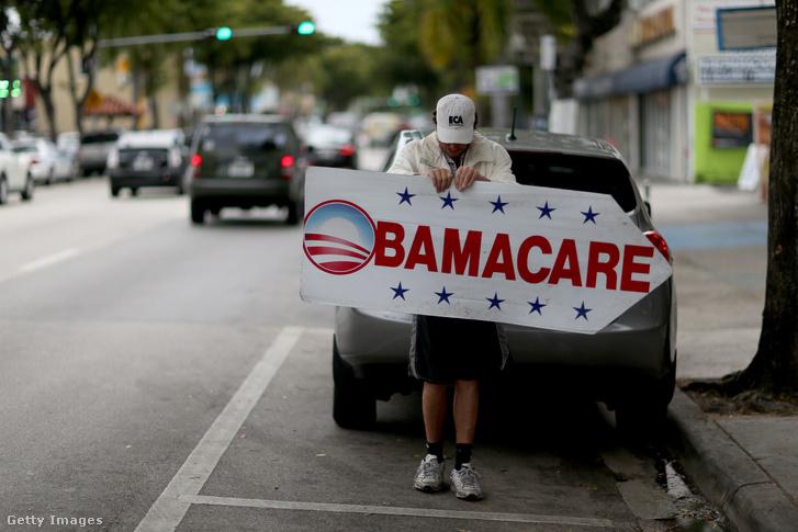 Egy férfi táblát tart, amivel egy biztosítótársasághoz irányítja az embereket, ahol feliratkozhatnak az Obamacare néven elhíresült ellátási törvényre 2015. február 5-én