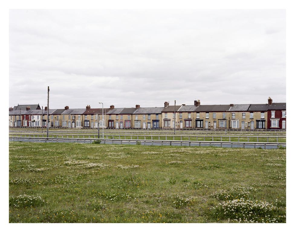 Liverpool. Külvárosi helyzet: lerombolásra ítélt munkáslakások, az előtérben a már eltűnt házak helyén a befüvezett építhető telkek sorai. A szegények kiszorulnak, helyükre, az újépítésű lakásokba gazdagabb családok költöznek. A szociális lakáshiány itt sem megoldott probléma.