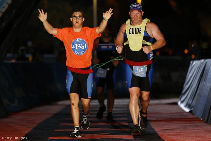 Chris Nikic ás vezetője Dan Grieb átfut az Ironman Florida célján 2020. november 7-én