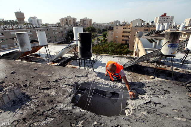Palesztin rakéta által ütött lyuk egy lakóépület tetején a dél-izraeli Askelónban