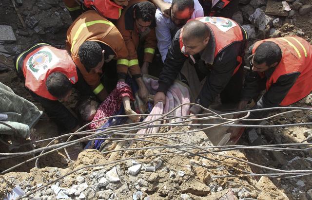 A palesztin polgári védelem tagjai kimentenek egy túlélőt egy összedőlt épület romjai alól Gázavárosban