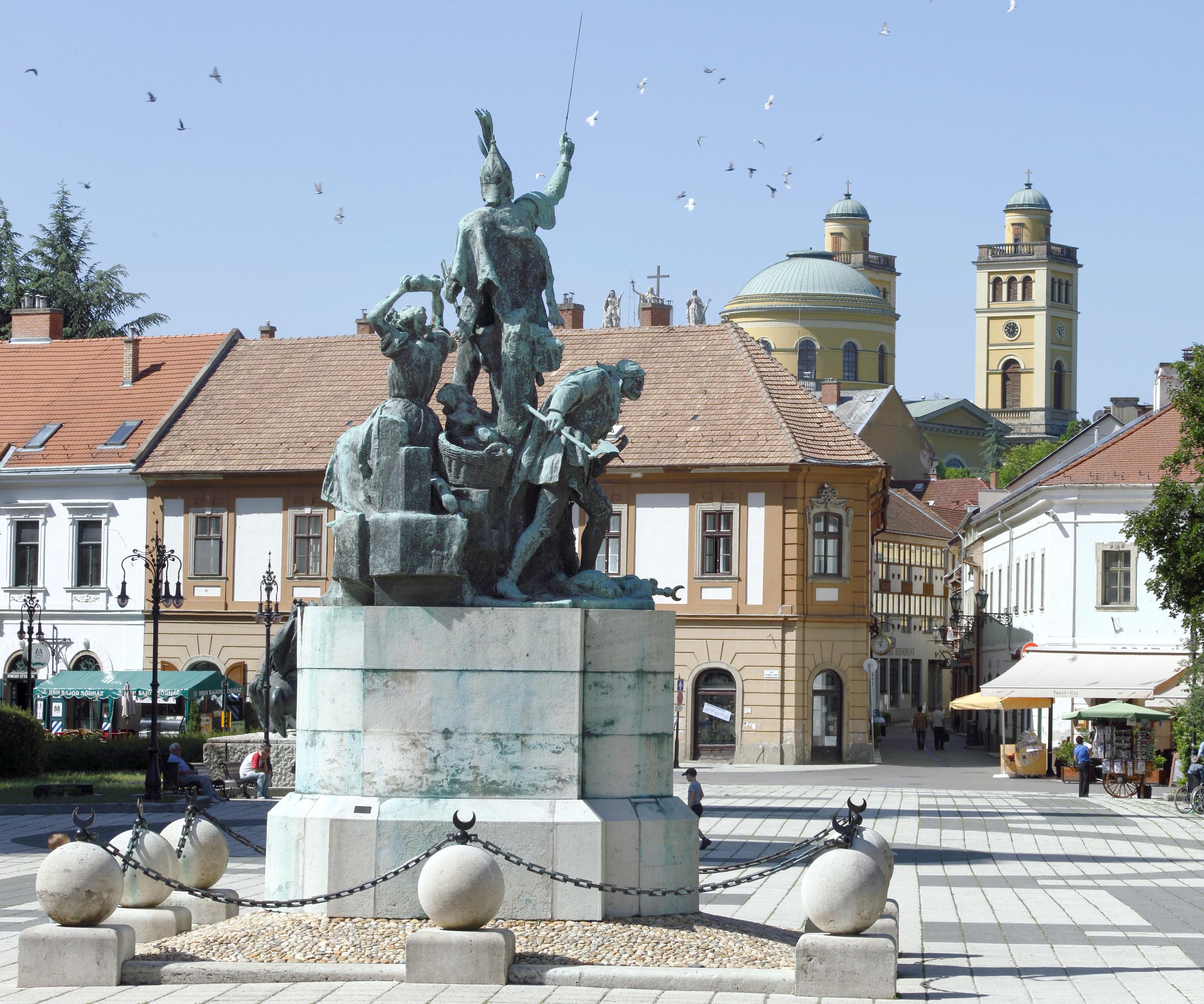 Melyik város főtere, fontos szoborcsoportja és templomi kupolája látható a képen?