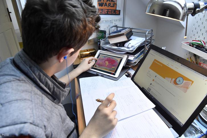 A digitális távoktatás keretében előírt feladatokat old meg egy gimnazista fiú