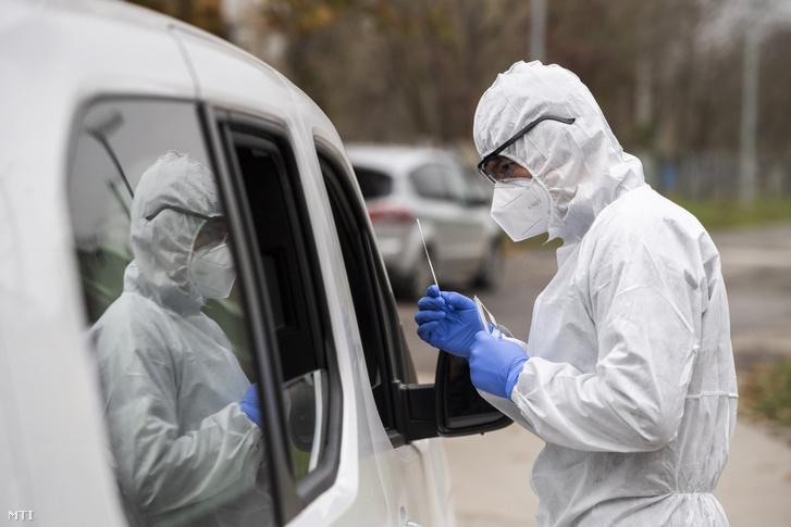 Koronavírusteszthez vesz mintát az Országos Mentőszolgálat munkatársa Óbudán 2020. november 13-án.