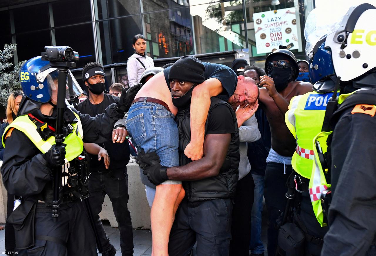 Patrick Hutchinson tüntető egy sérült ellentüntetőt visz biztonságos helyre a Black Lives Matter tüntetésen Londonban, 2020. június 13-án.