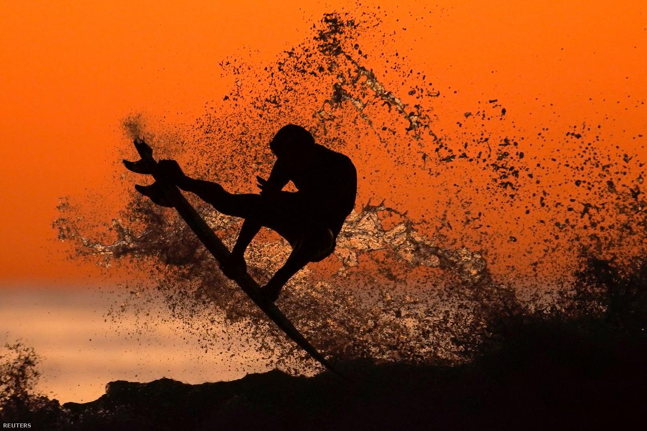 Egy szörfös meglovagol egy hullámot napszállta után a kaliforniai Cardiffban 2020. január 7-én.