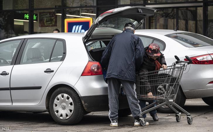 Idős vásárlók pakolnak autójuk csomagtartójába egy üzlet előtt