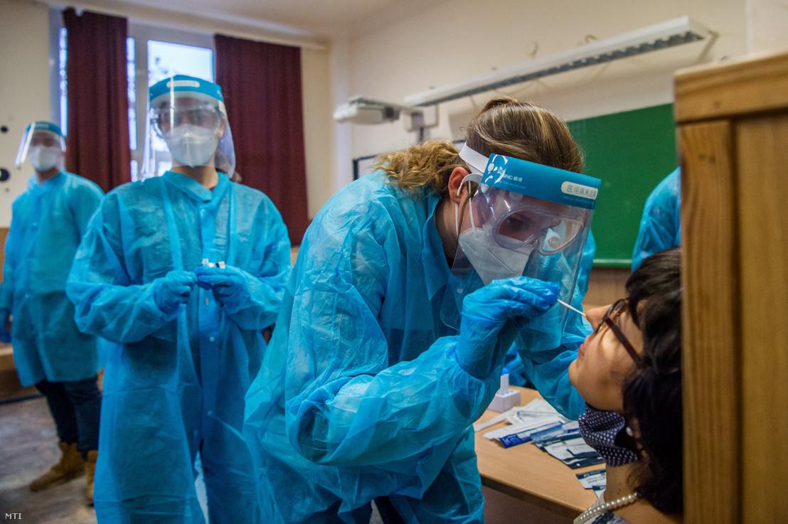 Koronavírustesztet végző orvostanhallgatók mintát vesznek a budapesti iskola egyik dolgozójától Budapesten 2020. november 26-án