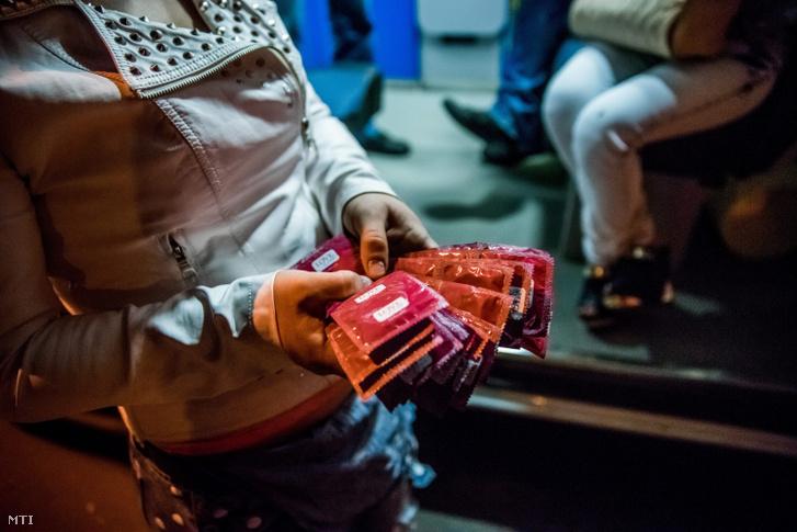 Egy Bukarest utcáin dolgozó szexmunkás az AIDS terjedése ellen küzdő Asociata Romana Anti-Sida (ARAS) romániai alapítványtól kapott óvszerekkel a kezében