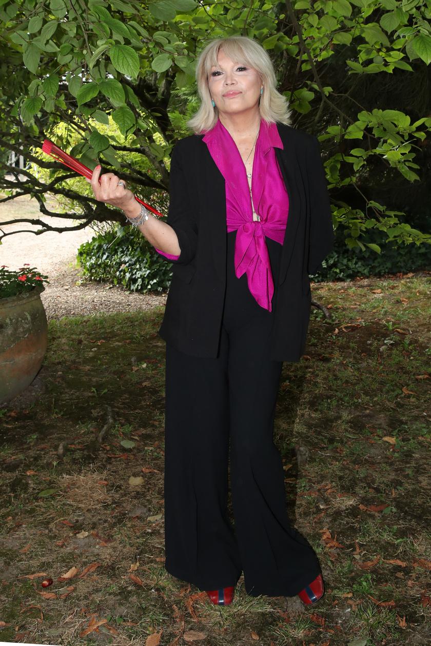 Amanda Lear előszeretettel visel élénk színeket, amelyek még nőiesebbé, fiatalosabbá teszik a megjelenését. Ez a lilás blúz remekül kiegészíti a fekete szettet.