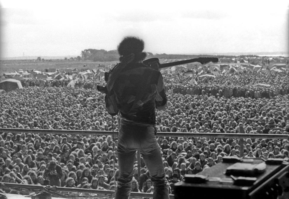 Jimi Hendrix az egyik legendás trükkjével a tömeg előtt. Neki tulajdonítják azt a találmányt, amikor a gitáros a fogaival szólózik a hangszerén. Hendrix ezen kívül még a háta mögött is szeretett játszani, illetve fel is gyújtotta a gitárját egy-egy extatikus pillanatában.