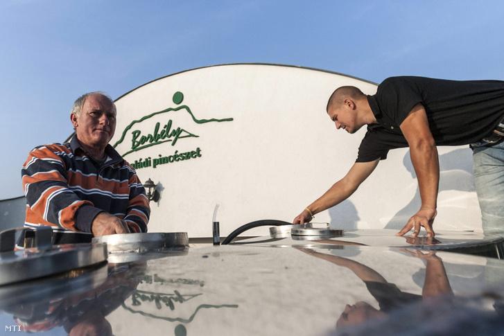 Borbély Gyula tulajdonos (b) és fia Borbély Tamás (j) a kiforrt bort fejti át egy krómacél tartályba a Borbély Családi Pincészet szőlőjében Badacsonytomajban 2012. szeptember 18-án