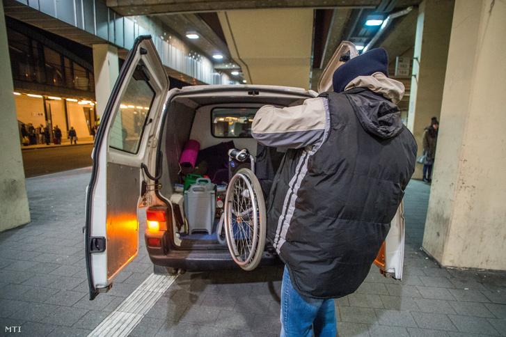 Az otthontalanokat segítő Menhely Alapítvány 24 órában működő krízisautó-szolgálatának munkatársa mozgássérült hajléktalan férfi kerekesszékét teszi kisbuszba