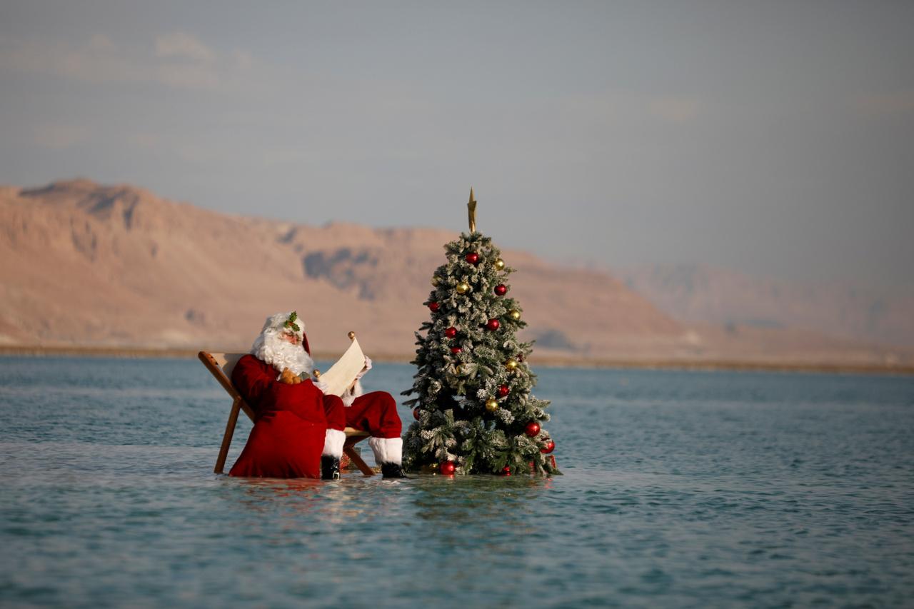A Mikulás a Holt-tenger egy sóképződményén pihenve ráérősen olvassa át a gyerekek kívánságait.