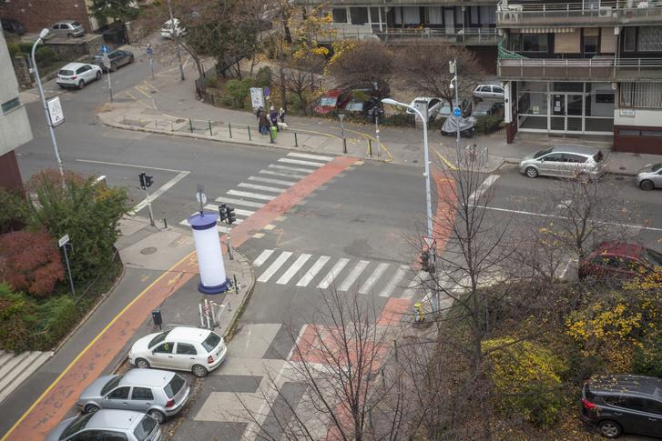 """A kereszteződés madártávlatból, a Kacsa utca irányából. Jól látszik, ahogy túloldalon ketté válik a kerékpárút, és foglalja keretbe a kereszteződést. Innen nagyívben balra fordulva, a zebrát és a Széna tér felé """"egyirányú"""" kerékpárutat keresztezve lehet a Margit körútra eljutni, míg jobbra a Csalogány utca van irányban."""