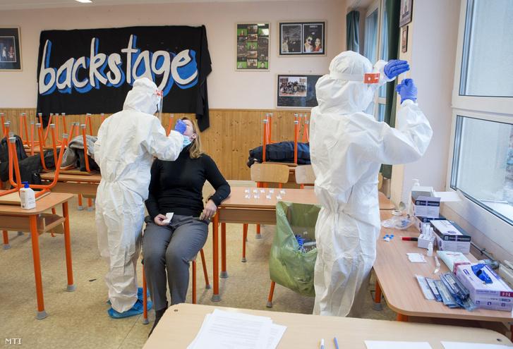 Koronavírusteszthez vesz mintát a Széchenyi István Egyetem hallgatója a győri Móra Ferenc Általános Iskola dolgozójától az intézményben 2020. december 4-én