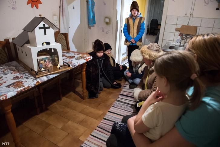 A Szent Jakab-plébánia hittanos diákjai Papp Erzsébet hitoktató vezetésével betlehemeznek egy családnál a Jász-Nagykun-Szolnok megyei Csépán 2019. december 18-án.