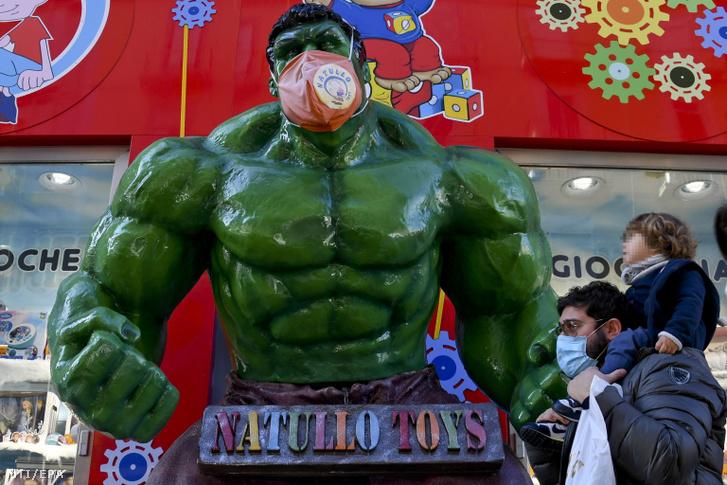 Védőmaszk egy életnagyságú Hulk-figurán egy nápolyi játékbolt bejáratánál 2020. december 16-án