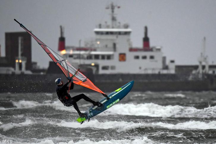 Szörfös használja ki a közeledő Bella vihar által felkorbácsolt hullámokat a Barassie strandnál Skóciában 2020. december 26-án