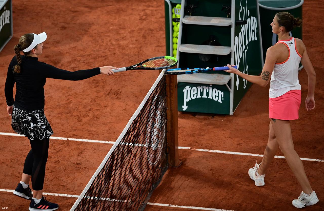 """A teniszezőknél a távolságtartásra is ügyeltek, a meccs végi pacsit felváltotta az ütők összeérintése. A képen Jelena Ostapenko Karolína Plískovával """"ütőzik"""" a mérkőzésük után."""