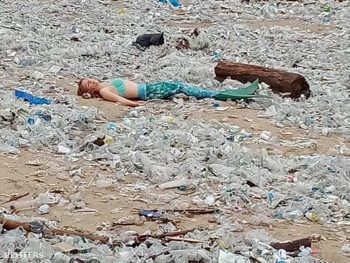 Sellőnek öltözött ember fekszik a Kuta strandon, ami szeméttel van tele Balin 2021. január 4-én