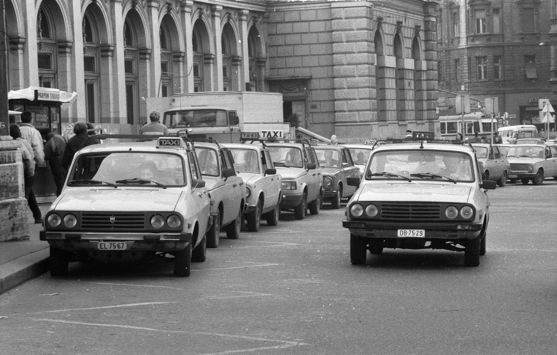 Az 1990-es képen milyen autókban vártak utasokra a taxisok a Keleti pályaudvarnál?
