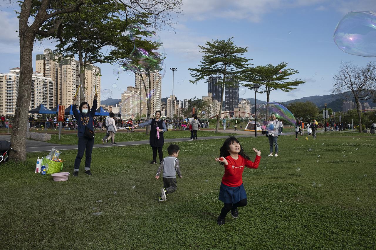 Gyerekek játszanak egy városi parkban, miközben a világban csúcsokat dönt az első hullám. Hszintien, 2020. március 29-én.