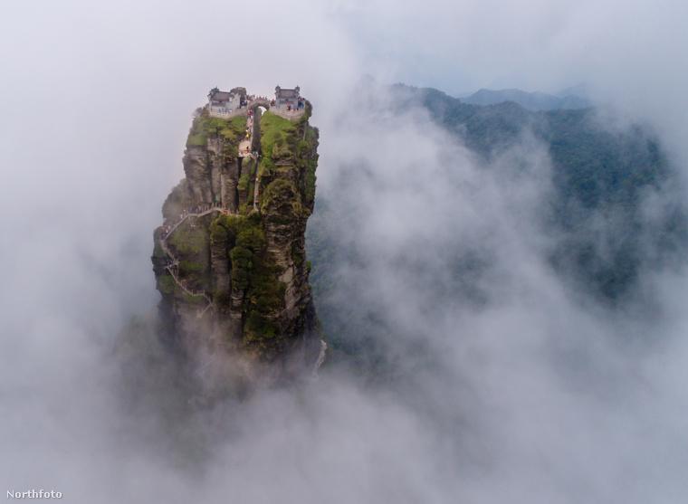Bár a ködtől/felhőktől annyira nem látszik, a háttérben a Wuling hegység körvonalai rajzolódnak ki.