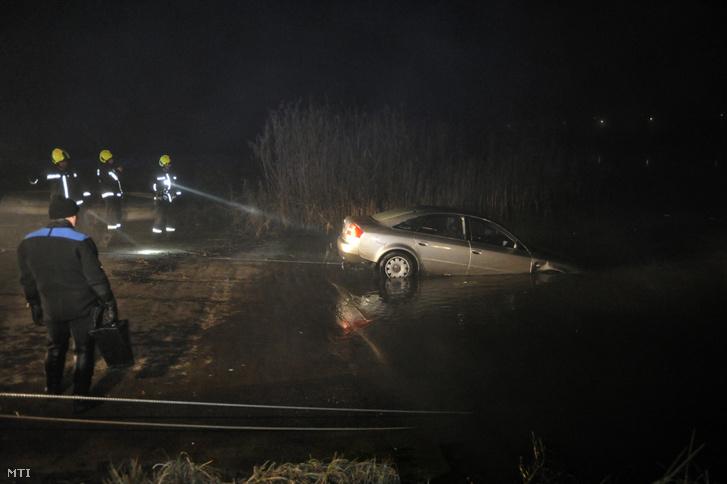 Tűzoltók vontatnak ki búvárok segítségével egy autót a Dunából a soroksári kompnál 2021. január 9-én.