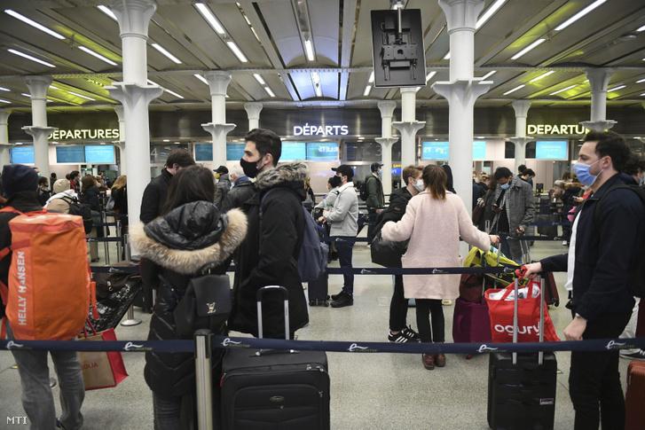 Sorban álló emberek a londoni St. Pancras állomáson 2020. december 20-án.