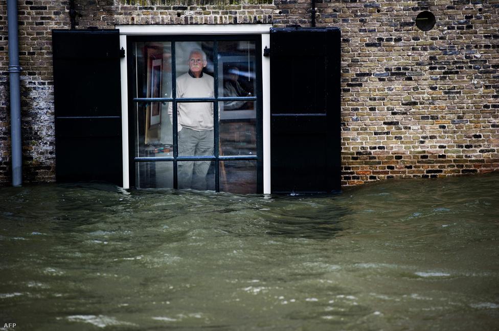 Egy férfi az elárasztott utcát figyeli ablakából Hollandiában. A 110 km/órás szél és a heves esőzések következében az utcákon hömpölygött a víz több holland tengerparti városban, mivel az ország negyede a tengerszint alatt fekszik. (Január 5.)