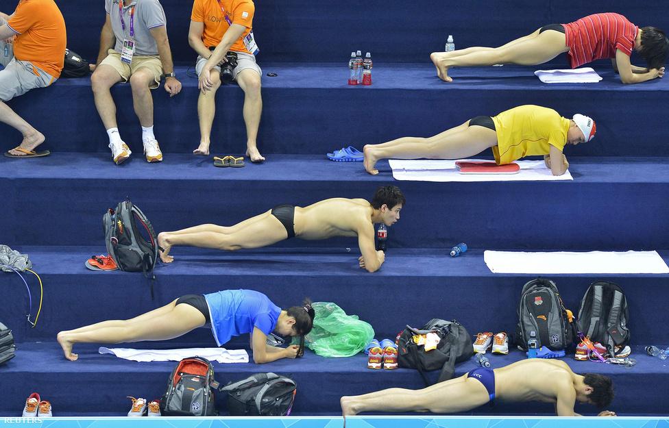Kínai úszók törzserősítő gyakorlatokat végeznek a londoni Aquatics Centreben, röviddel az olimpiai úszószámok kezdete előtt július 24-én.