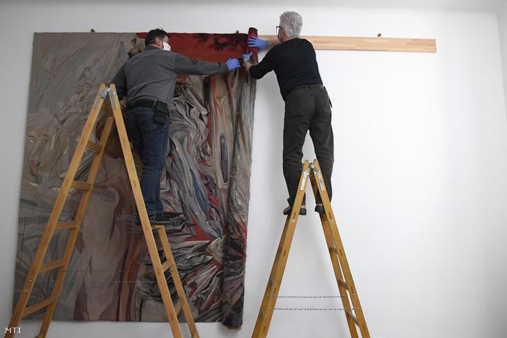 Az Iparmûvészeti Múzeum munkatársai leveszik a falról Tamás Klára képzõmûvész Dávidok és Góliátok címû alkotását a mûvész budapesti otthonában 2021. január 13-án.