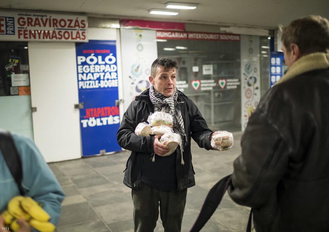 A Budapest Bike Maffia önkéntese nyújt át szendvicseket egy hajléktalannak