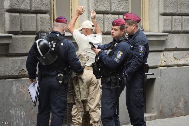 Egy férfit igazoltatnak a Mi Hazánk Mozgalomnak a Deák téri késelés áldozatairól tartott megemlékezése előtt az Országos Roma Önkormányzat székházánál 2020. május 28-án