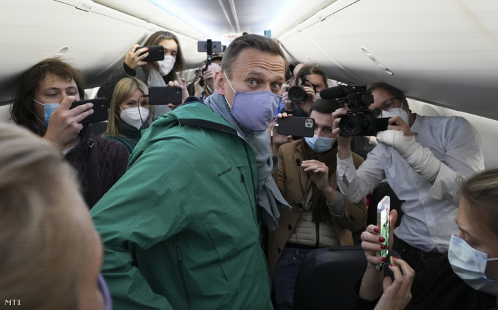 Alekszej Navalnij orosz ellenzéki politikust (k) körülveszik a sajtó képviselői egy Moszkva felé tartó repülőgépen a felszállás előtt a Berlin-Brandenburg Nemzetközi Repülőtéren Schönefeldben 2021. január 17-én.