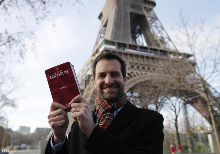 Gwendal Poullennec, a Guide Michelin francia éttermi kalauz igazgatója kezében az új, 2021-es kiadvánnyal a párizsi Eiffel-torony előtt 2021. január 18-án.
