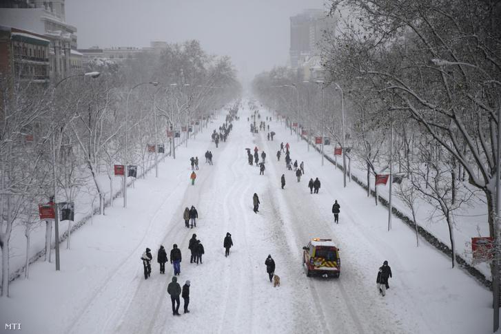 Járókelők mennek a madridi Paseo de la Castellana sugárúton a hóesésben 2021. január 9-én