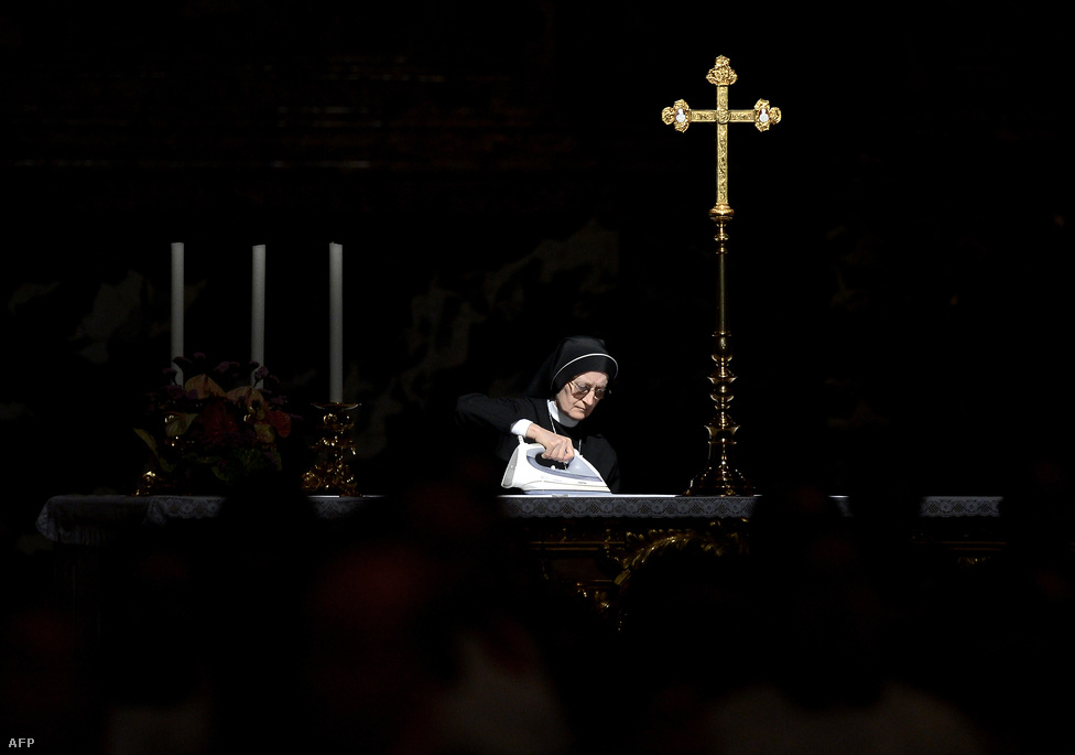 Apáca vasalja a Szent Péter Bazilika egyik mellékoltárán a terítőt pünkösd vasárnapján, május 27-én, Rómában.