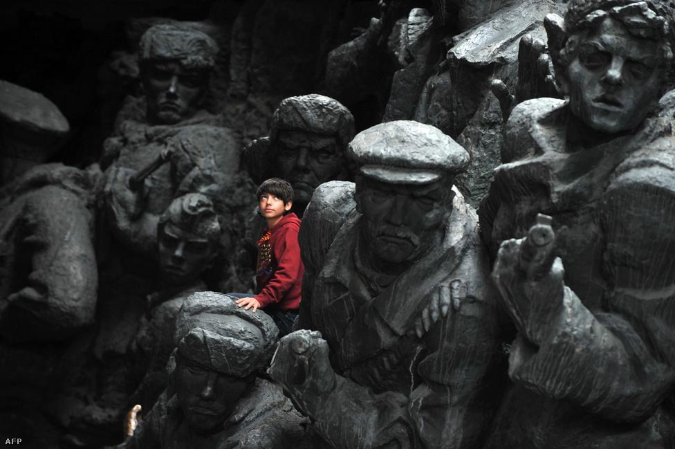 Kisfiú mászik egy kijevi háborús emlékművön május 9-én, a Győzelem Napja ünnepségen.