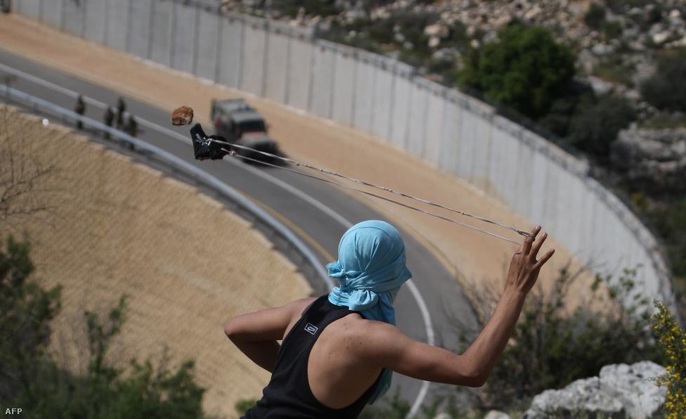 Izraeli járőröket céloz meg parittyájával egy palesztin fiatal Bilin község közelében az Izrealt Ciszjordániával elválasztó falnál április 13-án.