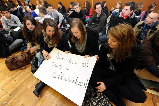 Diákok Nem kel töb pénz a zoktatásban! feliratú transzparenst tartanak a kormány felsőoktatást érintő intézkedései ellen tartott ülősztrájkon a pécsi Leőwey Klára Gimnáziumban