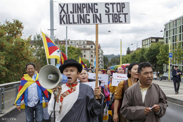 """Megafonba beszél egy """"Hszi Csin-ping, hagyd abba az öldöklést Tibetben!"""" jelentésű transzparenst tartó férfi a tibetiek és ujgurok kínai elnyomása elleni tüntetésen az ENSZ genfi székházánál, 2016. szeptember 16-án"""