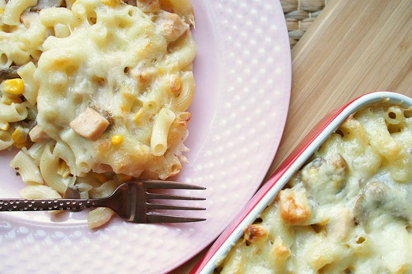 Sütőben sült rakott tészta pirult, olvadt sajttal borítva: sonka, gomba és kukorica gazdagítja