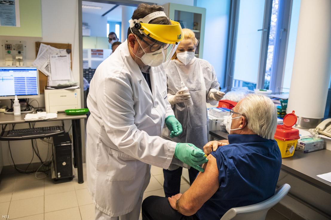 Merkely Béla, a Semmelweis Egyetem rektora beoltja a Pfizer és a BioNTech által kifejlesztett koronavírus elleni oltóanyaggal Ludwig Endre infektológust a Városmajori Szív- és Érgyógyászati Klinikán, 2020. december 26-án