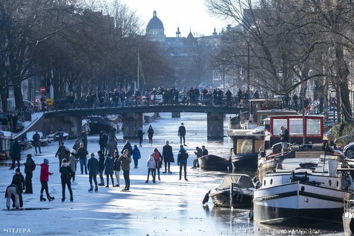 Emberek nézik egy hídról a befagyott Prinsengracht-csatornán korcsolyázókat Amszterdamban 2021. február 13-án
