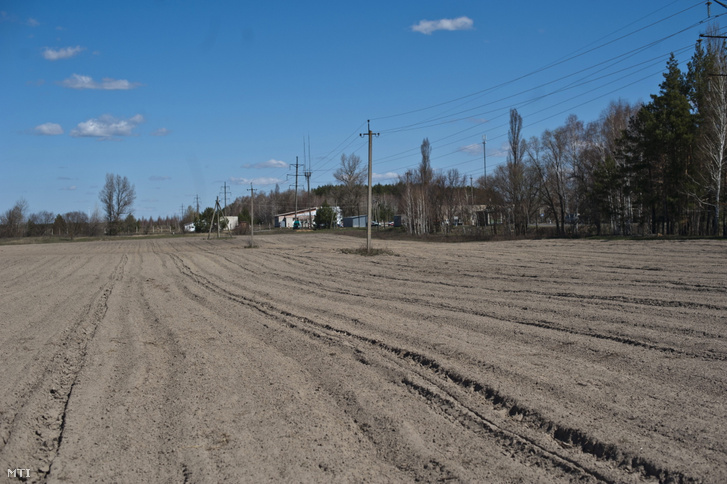 Megművelt szántóföld Ditytkiben, a csernobili zóna határában, a kerítéstől néhány méterre. Jobbra, a fehér épület a zóna bejárata. Ditytki egykor a környék leggazdagabb települése volt kiváló termőföldje miatt.