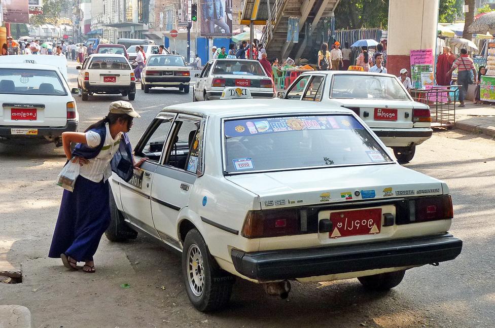 Nagyvárosi forgalom. Yangonban a taxik aránya legalább akkora, mint New Yorkban, de az állomány összetétele erősen különbözik: kivénhedt japán szedánok állnak az utasok rendelkezésére. Műszaki és esztétikai állapotukban nagy a szórás, de feladatukat: burmai mércével jó pénzért elvinni az utast A-ból B-be, betöltik.