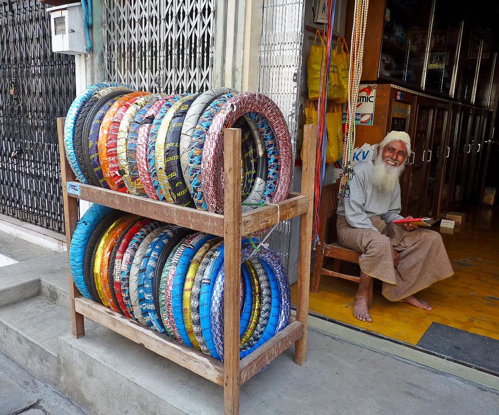 Kereskedéspszichológiai alaptudnivaló, hogy a színek vonzzák a szemet, és ezzel a vevőket. Hatványozottan igaz ez Dél-Ázsiában, ahol az emberek imádják az élénk színeket. Ezért már gyárilag csilli-villi csomagolásba burkolják a gumiabroncsokat. Az eredmény, mint ennél a Mandalay-i kereskedőnél is látjuk: vidám színorgia.