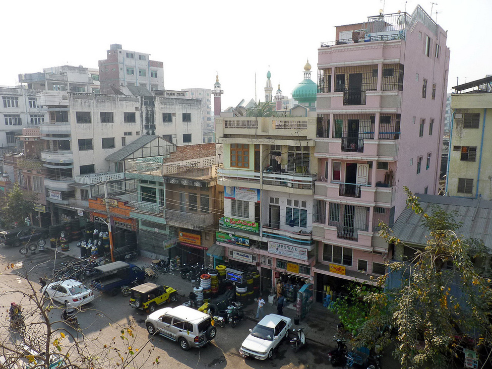 Tipikus yangoni utcarészlet, az épületek földszintjén a közlekedést kiszolgáló üzletsorral. A négymilliós Yangonban, az egykori fővárosban, Burma gazdasági-pénzügyi központjában erős a forgalom, de korántsem éri el a Bangkokra, vagy Saigonra jellemző sűrűséget. A járműállomány szemlátomást fiatalodik, de a derékhadat még mindig a 70-es, 80-as évek japán autói adják.